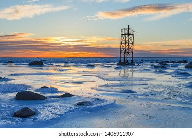 Monk on the abandoned military watching tower, orange sunset over frozen sea coast