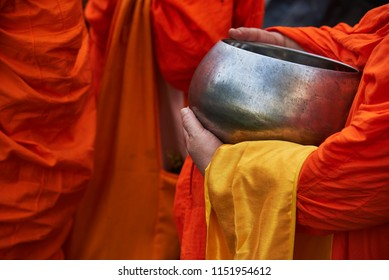 A monk in orange robe holding an alms bowl for food offering in the morning