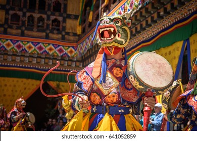 Monk playing the drums and dacing at colorful mask dance at yearly Paro Tsechu festival in Bhutan