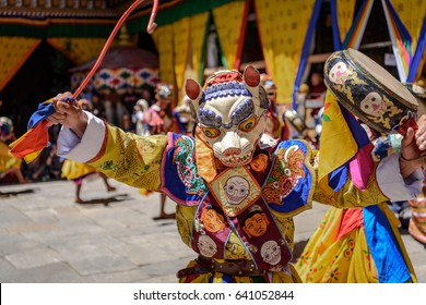 Monk raising his drum at colorful mask dance at yearly Paro Tsechu festival in Bhutan