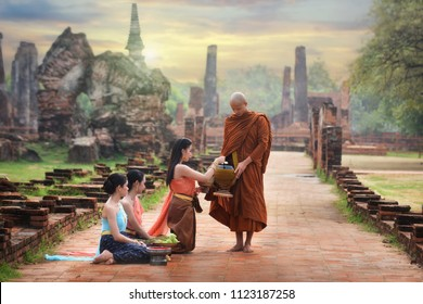 Monk receiving food and items offering from people at Three ancient pagoda, Wat Phra Sri Sanphet where is the public place, Ayutthaya Historical Park, Thailand