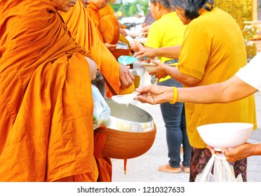 monk reciving food and many things from poeple. it is south east Asia culture