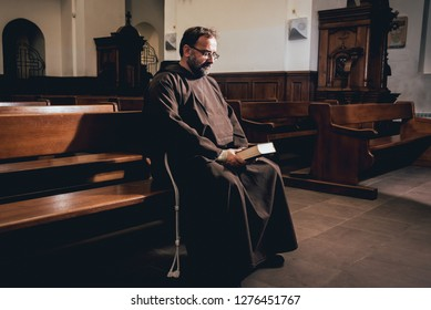 A monk in robes with holy bible in their hands praying in the church. Background