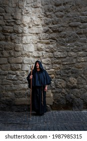 A monk with a staff at a textured stone wall, light falling on him from above. Concept: prayer and magic, the descent of the spirit, God's protection and healing, the power of prayer.