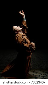 Monk standing on kneels and asking God for help