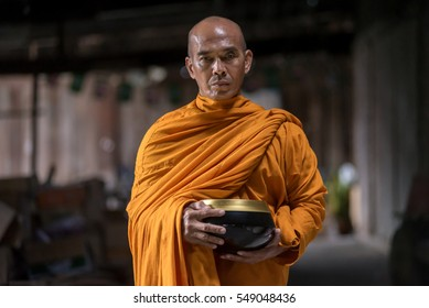 A monk in Thailand. Buddhist monks are walking on a routes between rural villages.