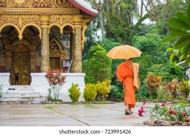 Monk with an umbrella on a city street, Louangphabang, Laos. Copy space for text
