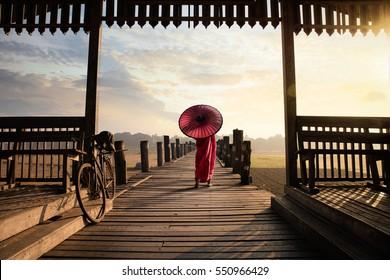 Monk walk on the wooded bridge, U Bein Bridge, Mandalay Myanmar