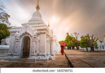 A monk walk with red umbrella at stupa in Kuthodaw Pagoda,  Kuthodaw is a Buddhist stupa, located in Mandalay, Burma (Myanmar) with sun exposer sky background.