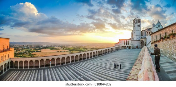 Monk walking towards famous Basilica of St. Francis of Assisi (Basilica Papale di San Francesco) with panoramic view of Lower Plaza and golden fields and hills at sunset in Assisi, Umbria, Italy