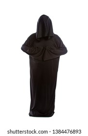 Monk wearing black robes and a hood or a person in a halloween costume of a grim reaper ghost.  The image depicts a priest in traditional or ancient clothing.