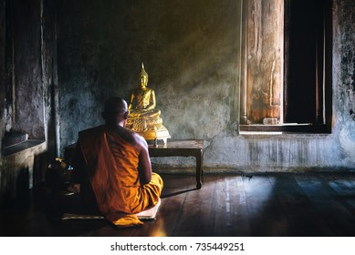 A monk is worshiping and meditating in front of the golden Buddha as part of Buddhist activities.Focus on the Buddha