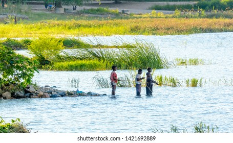 Monkey Bay/Malawi - March 21 2018: boys stand in Lake Malawi fishing with home made fishing rods