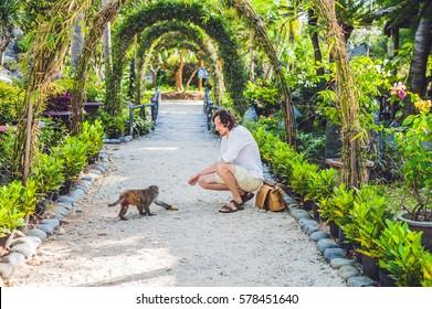 The monkey eats a banana in a tropical garden.
