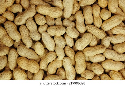 Monkey nuts, peanuts or groundnuts in shells as an abstract background texture