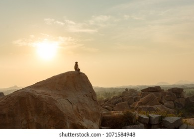 The monkey sees off the sunset. Incredible landscape with a wild monkey, sitting on a rock among the mountains.
