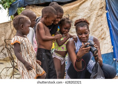 Monkey Village, LAGOS, NIGERIA. April, 2017: A photographer showing little children some pictures on her camera after taking a few shots of them. Location: a village in Lagos, Nigeria