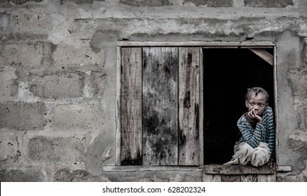 Monkey Village, LAGOS, NIGERIA. April, 2017: Street portrait of a young Nigerian girl named Queen sitting in a wooden window frame. Location: a village in Lagos, Nigeria called Monkey Village