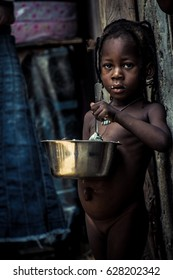 Monkey Village, LAGOS, NIGERIA. April, 2017: Candid portrait of a naked young Nigerian child/girl standing and eating. Location: a rural area/village in Lagos, Nigeria called Monkey Village