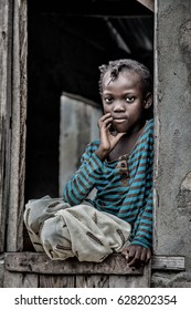 Monkey Village, LAGOS, NIGERIA. April, 2017. Street portrait of a young girl named Queen, sitting in a wooden window frame. Location: a rural area/village in Lagos, Nigeria called Monkey Village