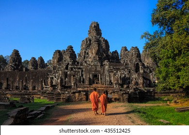 The monks in the ancient stone faces of Bayon temple, Angkor, Cambodia