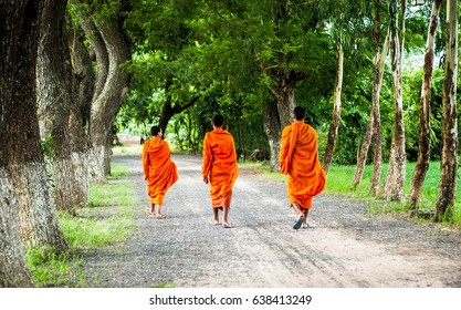 Monks with begging bowls beneath saffron robes go out in the morning in West Vietnam