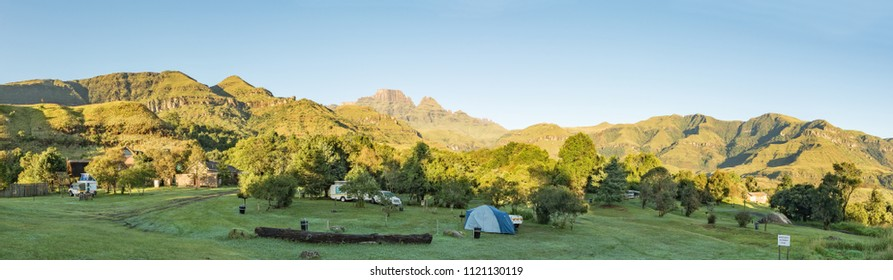 MONKS COWL, SOUTH AFRICA - MARCH 19, 2018: A tent, caravan and motorhomes at the camping site at Monks Cowl in the Drakensberg. Cathedral peak and Monks Cowl are visible in the back
