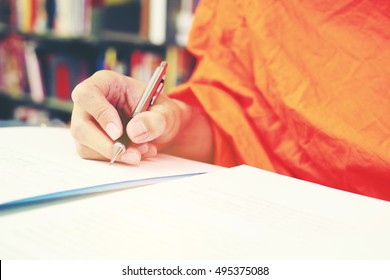 Monk's Hand writing in a book with the pencil