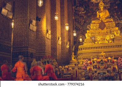 Monks meditating in orange robes in Bangkok golden temple
