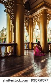 Monks meditating at religious site Shwedagon pagoda in Yangon, Myanmar