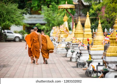Monks near buddhist gold temple in Thailand at the sunny day