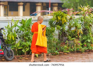 Monks on a city street in Louangphabang, Laos. Copy space for text. Vertical