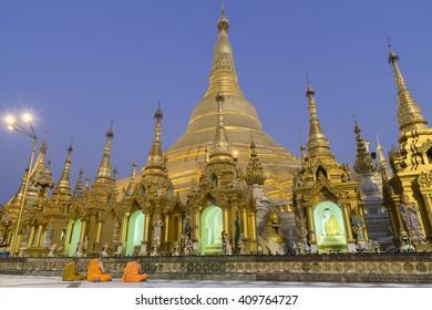 Monks praying at golden pagoda