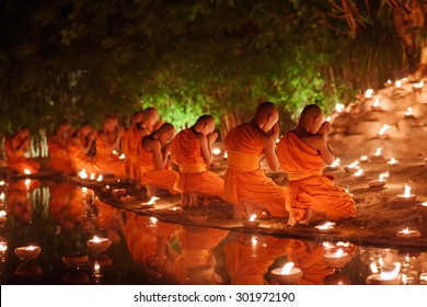 monks sitting meditate with many candle in Thai temple at night , Chiangmai ,Thailand, soft focus