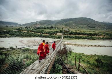 Monks walking over a bridge in Bhutan
