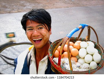 MON/MYANMAR - SEP 16. Unidentified local laughing boy carries a bascet with white and brown boiled eggs for sale on September 16, 2018 on the road in Mon State, Myanmar (Burma), Southeast Asia