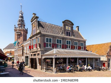 Monnickendam, The Netherlands on May 28, 2021; People on the terrace of a cafe in the former weigh house in the small picturesque fishing village of Monnickendam near Amsterdam.