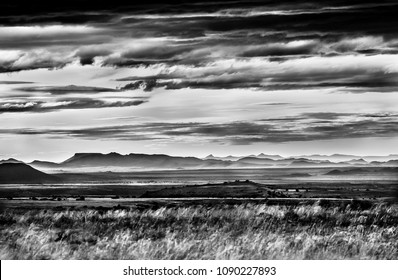 Mono chrome image of the vast African Karoo landscape with grassland, mountain ranges and dramatic sky and clouds.  Mountain Zebra National Park, South Africa