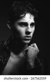 Monochromatic fashion portrait of handsome young man against dark  background