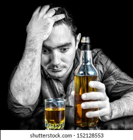 Monochromatic image of a drunk desperate hispanic  man with an whisky bottle isolated on black (the bottle and glass have color)