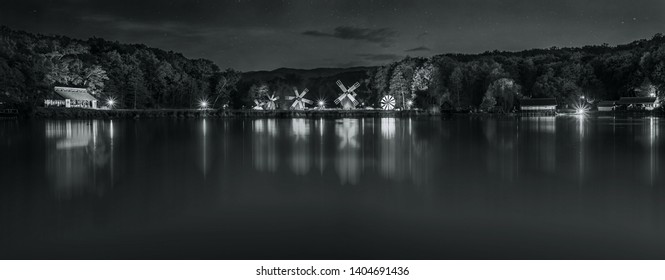 Monochromatic Landscape panorama with windmills at the blue hour in White Night of the Museums 2019. Dumbrava lake, Astra Museum of Traditional Folk Civilization, Sibiu city, Romania