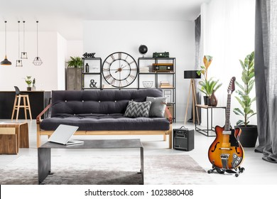 Monochromatic living room interior for a musician with black sofa, laptop on a coffee table and guitar near the window