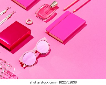 Monochromatic minimalist set of feminine accessories. High angle view of pink notepad, pencils, perfume flask and shiny jewellery. Femininity concept. Copy space