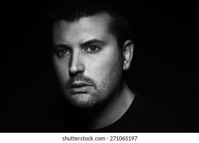 Monochromatic portrait of handsome young man against dark background