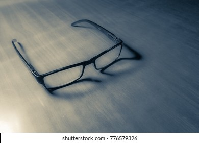 Monochromatic reading eyeglasses on a wooden surface with funny and skewed frame shadows