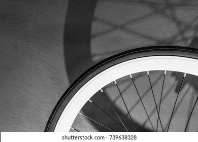 Monochrome of bicycle wheel with light and shadow, bicycle part, close up details, vintage background.