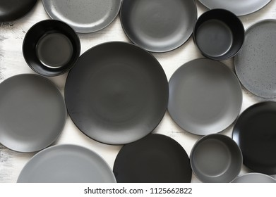 Monochrome black and grey tableware on white wood. Top view point, flat lay.
