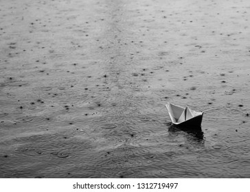 Monochrome black and white scene of a paper origami boat floating in water while raining with rain drops surrounding it.