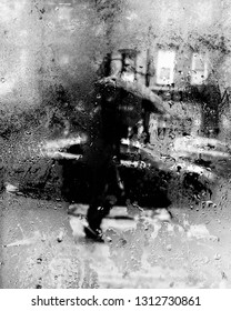 Monochrome black and white scene of a person walking with an umbrella outside while raining in the city, and watching from indoors with a foggy window.