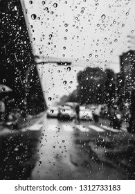 Monochrome black and white scene of a street during traffic and looking thru the back window of a car, with rain drops on the window.
